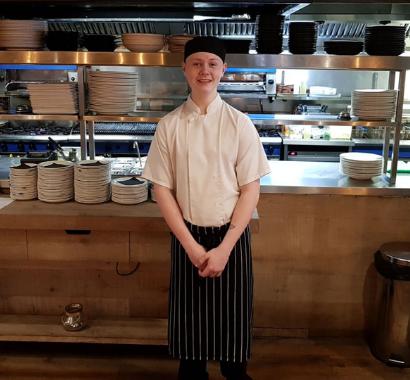 Apprentice Brandon in chefs whites in the kitchen